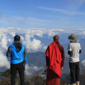 three men overlooking at clouds from the mountain