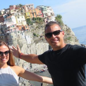 tourists posing with a village near a cliff as a backdrop