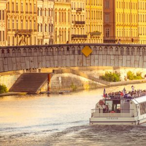 a sightseeing boat under a bridge during sunset