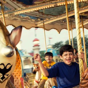 children riding carousel in imagica theme park