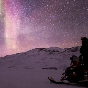 a man looking at the northern lights from his snowmobile