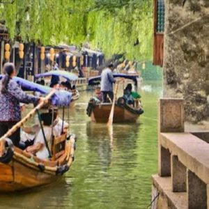 people riding on boats at zhouzhuang ancient town