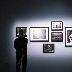 a guy looking at photos at Fotografiska Museum