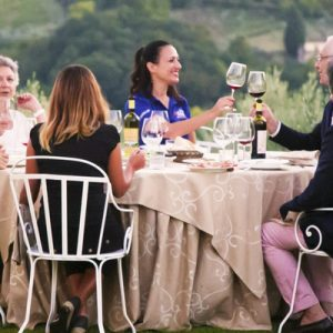 people eating and drinking wine in a vineyard