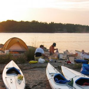two men setting up camp with tents and kayaks in stockholm archipelago