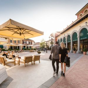 couple strolling the italian village-style outlet mall at serravalle designer outlet