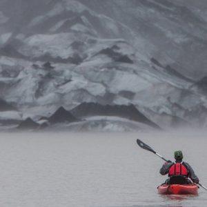 a lone kayaker somewhere in the Sólheimajökull Glacier Lagoon