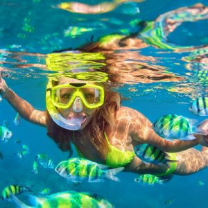 woman snorkeling among colorful fishes