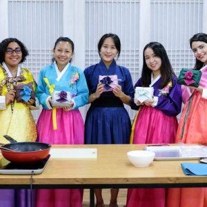 five women wearing hanbok at a korean cooking class