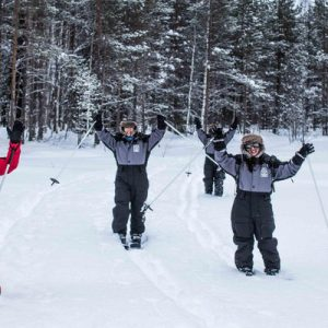 3 people in skiing gear with their hands up