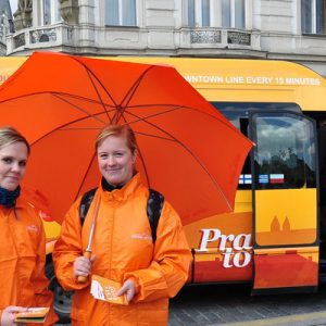 two women in orange in front of the sightseeing tour vehicle