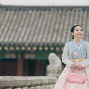 a girl in hanbok with handbag