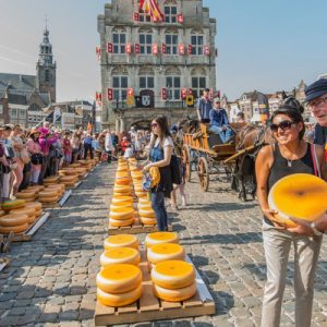 tourists posing with a long row of cheese