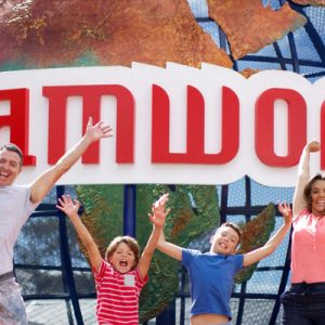 family jumping in front of the dreamworld globe in gold coast