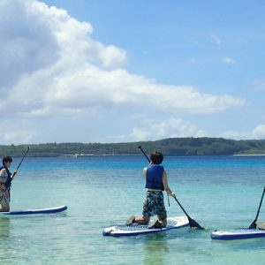 people standing on top of paddle boards somewhere in Guam