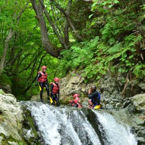 people at the top of waterfall in niseko, hokkaido during canyoning experience