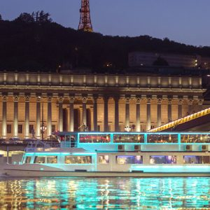 a large sightseeing ship at night with light reflecting in the waters