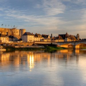 a view of Château d'Amboise from the river; you can see the bridge leading up to it; there's also a boat in the river