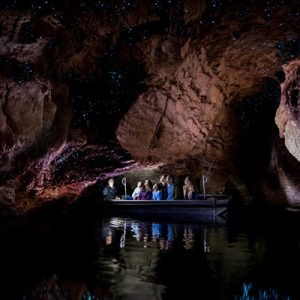 family riding a small boat in te anau glowworm caves