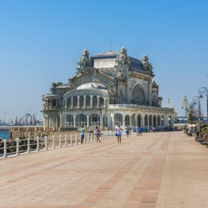 people walking on boardwalk in constanta near casino