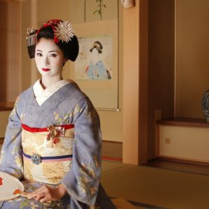 a maiko seated while holding a fan