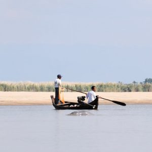 two men on a boat with an Irrawaddy dolphin