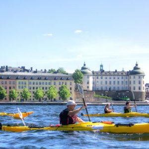 people kayaking next to buildings in stockholm