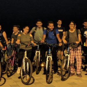 a group of tourists posing with bikes