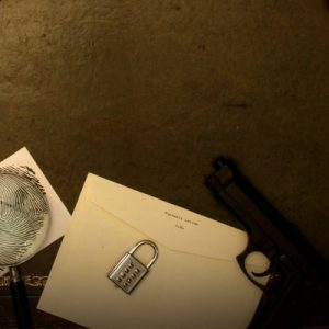 murder mystery case files and a gun on a table
