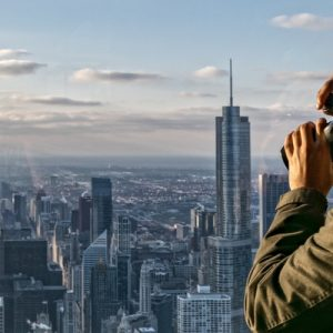 a man with binoculars at the 360 Chicago Observation Deck