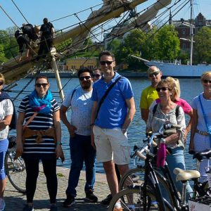 bike tour group standing next to ship in stockholm