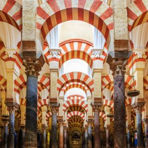 red and white painted arches inside the mosque-cathedral of cordoba