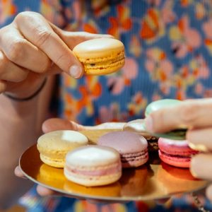 a platter of colorful macaroons and people are picking them up