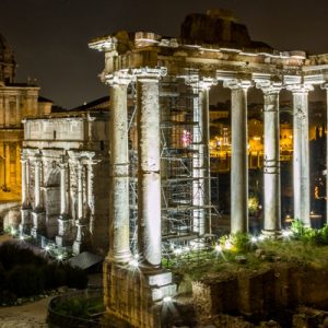 a shot of the Roman Forum; the pathways and columns are lit up by nightlights