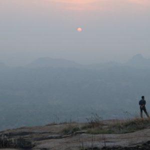 people watching the sunrise from Narayanagiri Hill's peak