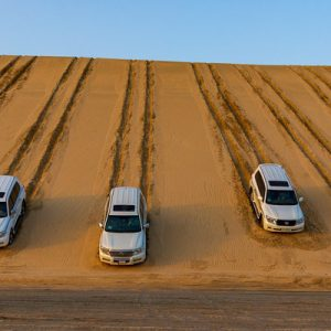 land cruisers driving down sand dune in doha desert