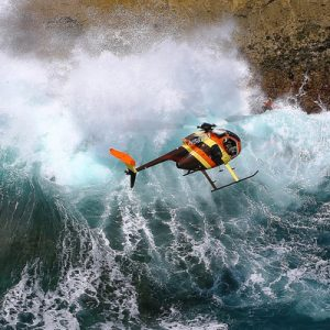 a helicopter flying over Oahu with a view of crashing waves