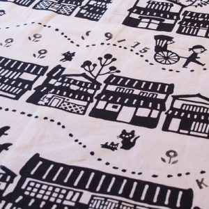 Japanese cotton towels on a table; there are drawings of people, animals, and houses