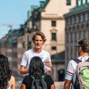 guests with tour guide with buildings behind them during the stockholm walking tour
