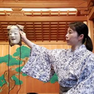 a japanese woman holding noh mask