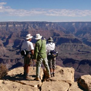 a panoramic view of the Grand Canyon and three people taking pictures of it