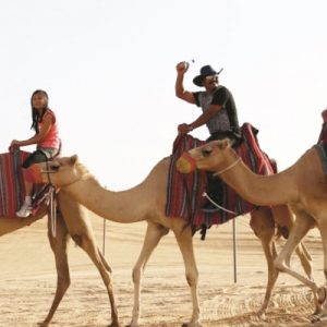 people riding camels in desert with guide for the camel trekking