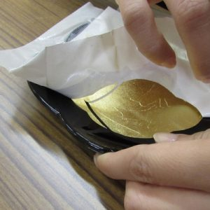 hands peeling off a gold leaf