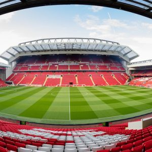 a panoramic shot of the Liverpool Football Club Stadium; the seats are either red or white