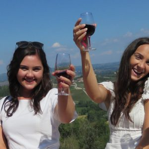 two ladies drinking wine with tuscany backdrop
