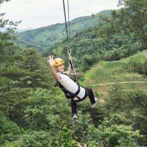 a tourist on a zipline waving at the camera