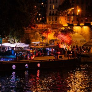 a view of the Seine River at night; there's a boat docked on the side