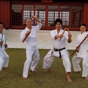 karate masters holding martial art weapons