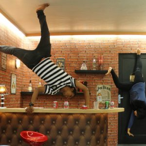 a couple posing upside down inside a bar themed space